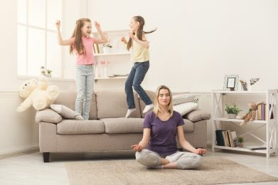 Young woman doing yoga exercise while daughters playing and having fun at home. Leasure, family, lifestyle concept
